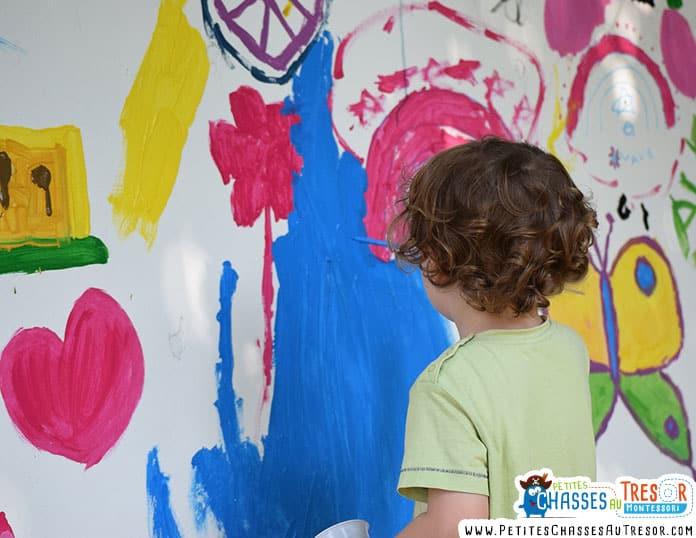 Enfant qui fait de la peinture sur un mur
