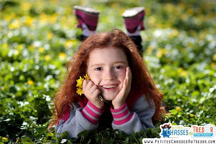 une petite fille est allongé dans un champ d'herbe